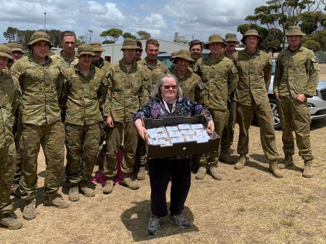 Barb giving muesli bars to the army on Kangaroo Island after the fires.